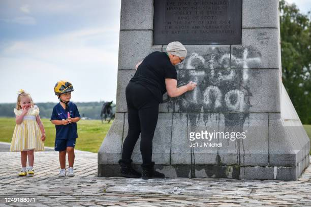 Children look on as a member of the public cleans the Robert the Bruce Statue which has been defaced with graffiti saying Racist King on June 12 2020...