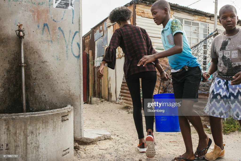 Children look on as a resident carries a plastic container filled with water from a communal tap in the Khayelitsha township, Cape Town, South Africa, on Friday, Feb. 9, 2018. Confronted by the worst drought on record after years of disastrously low rainfall, city authorities say they may have to turn off the water entirely on May 11, the famous 'Day Zero,' if reservoir levels keep falling and consumption doesn't slow enough. Photographer: Waldo Swiegers/Bloomberg via Getty Images