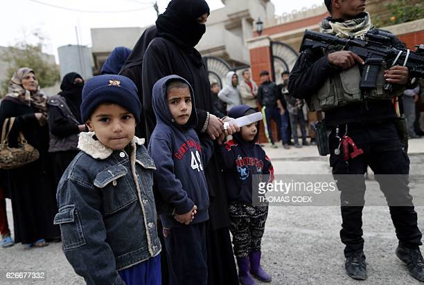 Children look on as a soldier from the Iraqi special forces stands guard during a food distribution organised by the ministry of displacement and...