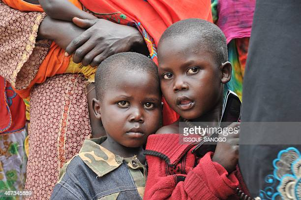 Children look on as Chadian nationals and others from other moslem countries fleeing interreligious violence wait in front of the Bangui air force...