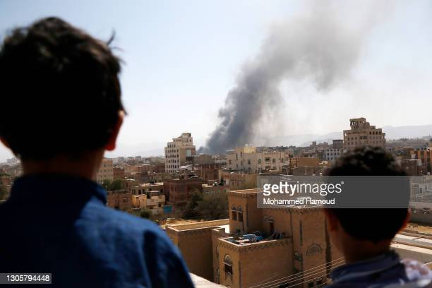 Children look on as smoke billows above the residential area following airstrikes of the Saudi-led coalition targeting Houthi-held military positions...