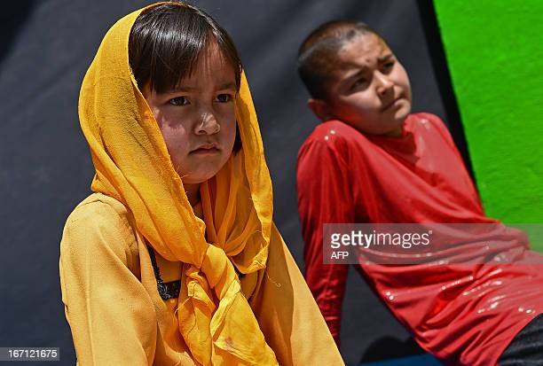 """Children look on as young Afghans from The Mobile Mini Circus for Children take part in a performance to honour """"World Circus Day"""" at Their Centre in..."""