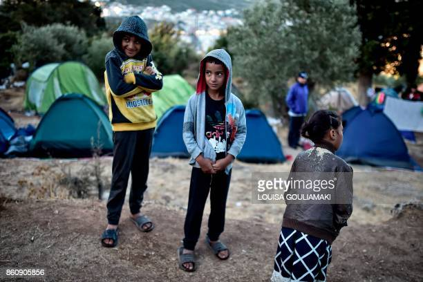 Children look on at a makeshift tent camp near the overcrowded hotspot on the Greek eastern Aegean islands of Samos on October 13 2017 More than 3000...