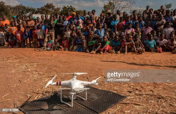 Children look on during a drone safety and awareness demonstration on June 22 in regards to humanitarian drone corridor testing under the...
