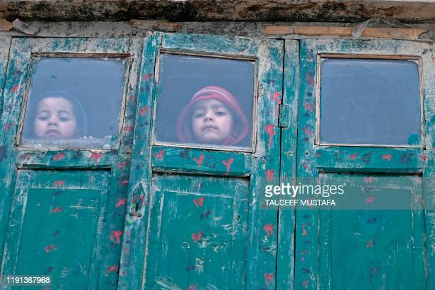 TOPSHOT Children look on from a mud house during a cold day on the outskirts of Srinagar on January 3 2020