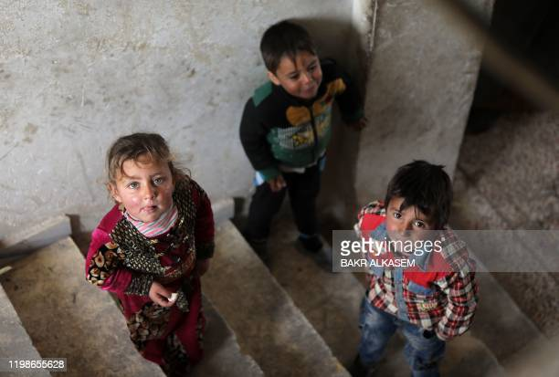 Children look on in the stairwell of a house in the vicinity of the northern Syrian town of Tal Abyad on February 4 where many families from the...