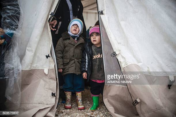 Children look out of a tent as they wait to board a bus with other migrants and refugees in the southern Serbian town of Presevo on January 6, 2016....
