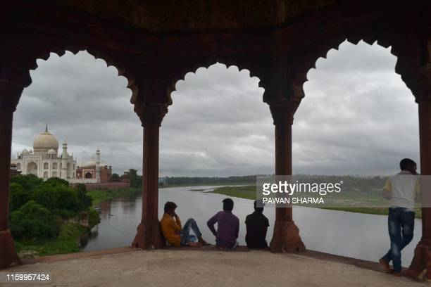 Children look out over the Yamuna River and the Taj Mahal mausoleum in Agra in Uttar Pradesh state on August 6, 2019.