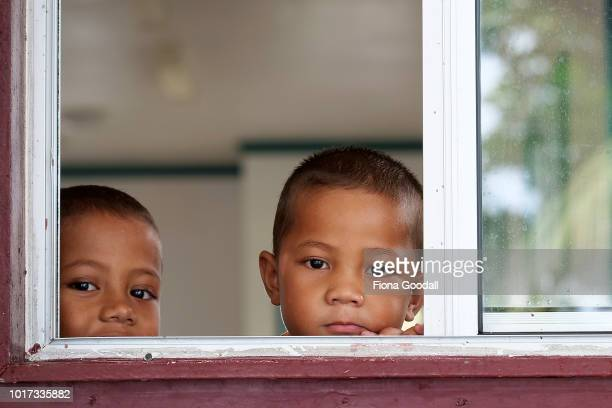 Children look out the church window on August 15 2018 in Funafuti Tuvalu Sunday is a day of family and church There are many churches on the mainland...