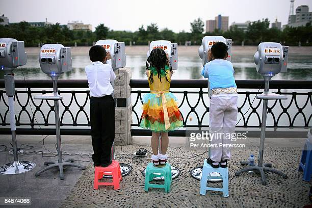 Children look through binoculars in Kurle, China.
