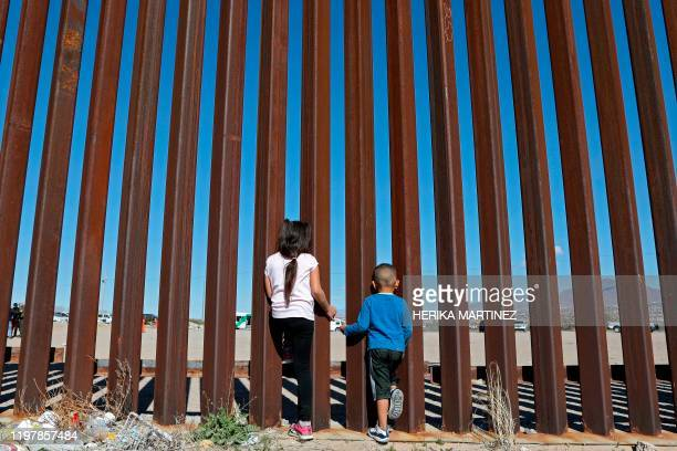 Children look through the border fence in Ciudad Juarez, Chihuahua state, Mexico, on January 31 as U.S. Border Patrol agents conduct a training...