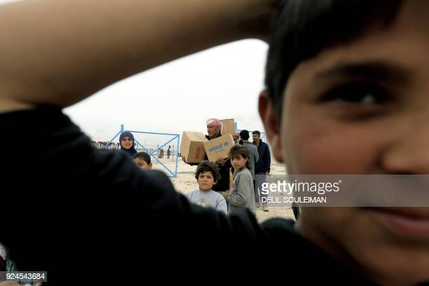 TOPSHOT Children look towards the camera as a displaced Syrian who fled his homes in Deir Ezzor city carries boxes of humanitarian aid supplied by...