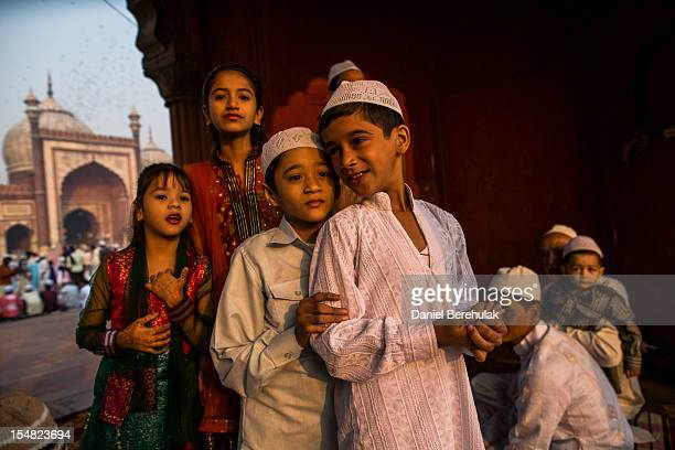 Children look towards the sound of ceremonial blast ahead of prayer time on as Indian Muslims gather for Eid alAdha prayers at Jama Masjid on October...