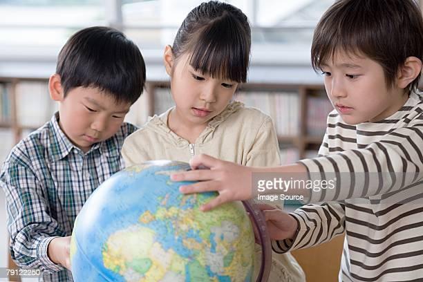 Kinder, die auf einem Globus
