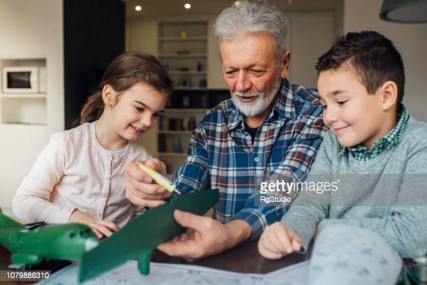 blick auf einen mann, der eine spielzeug kinder - kunsthandwerkliches erzeugnis stock-fotos und bilder