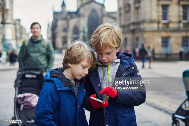 children looking at a smart phone together - edinburgh scotland stock pictures, royalty-free photos & images