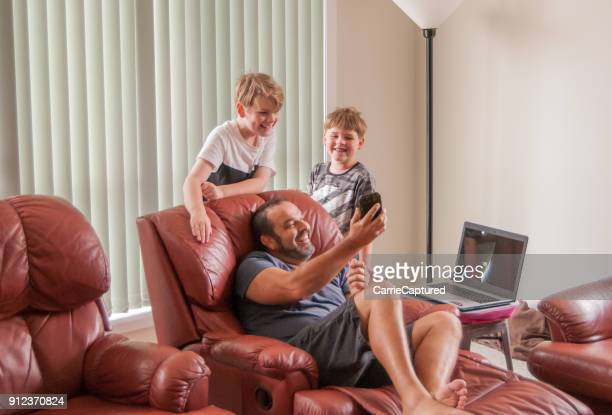 children looking at device held by man relaxing in recliners - reclining chair stock photos and pictures