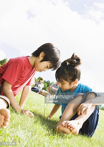 children looking at flower - male feet on face stock photos and pictures