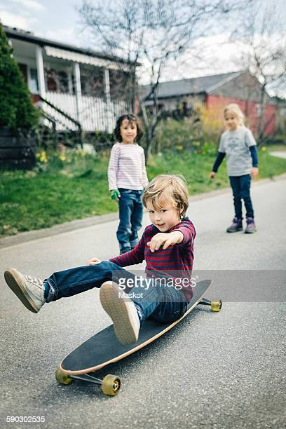 Children looking at friend skateboard on footpath outside house
