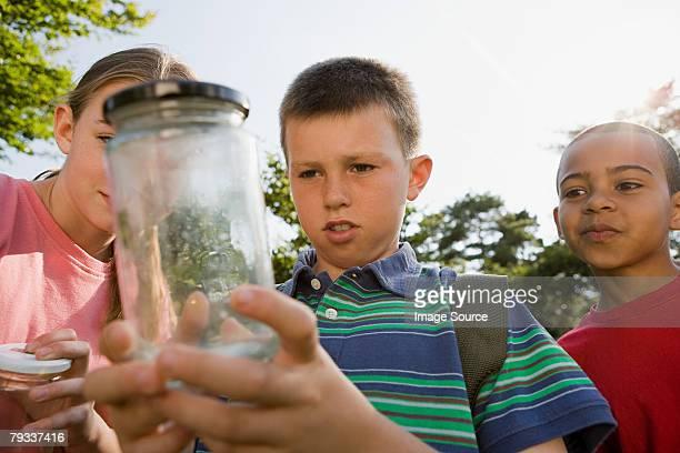 Children looking at jar