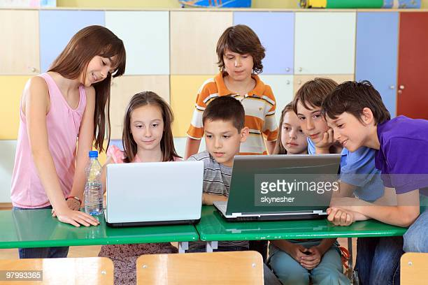 Children looking at laptop computers in classroom.