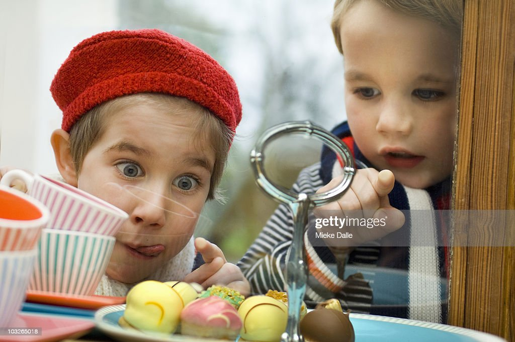 Children looking at little cakes in window display : Stock Photo