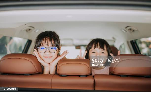 2 children looking at the camera from inside of a car smiling happily