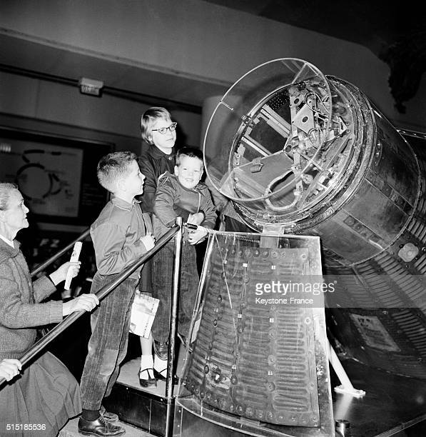Children Looking At The Capsule Of Astronaut John Glenn On Which He Made Three Turns Around The Earth At the Palais De La Découverte in Paris France...