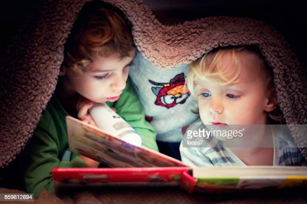 Enfants à la recherche dans le livre sous la couverture