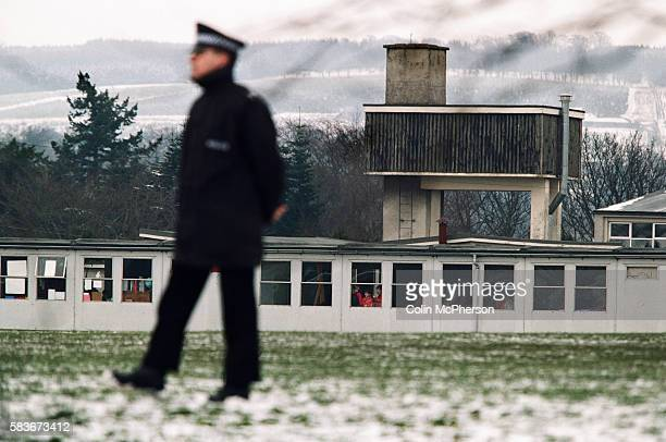 Children looking out of a classroom window as a police officer stands guard at Dunblane primary school Scotland shortly after the shooting incident...