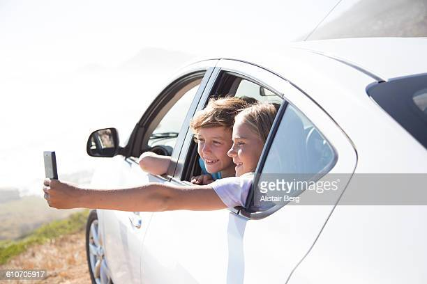 Children looking out of car overlooking a beach