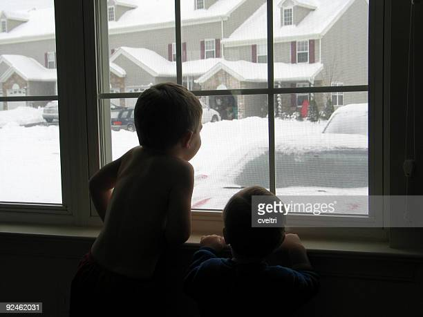 Children Looking out Window During Snow Storm on Winter Day