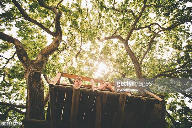 Children looking over side of treehouse with lush green leaves