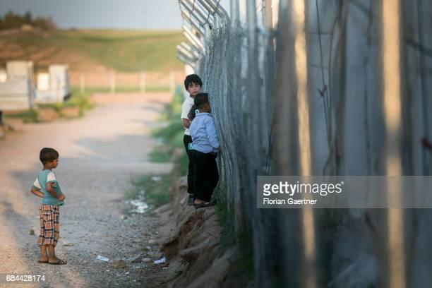Children looking through a fence in the refugee camp 'Hasansham U3' near Hasansham on April 20 2017 in Hasansham Iraq