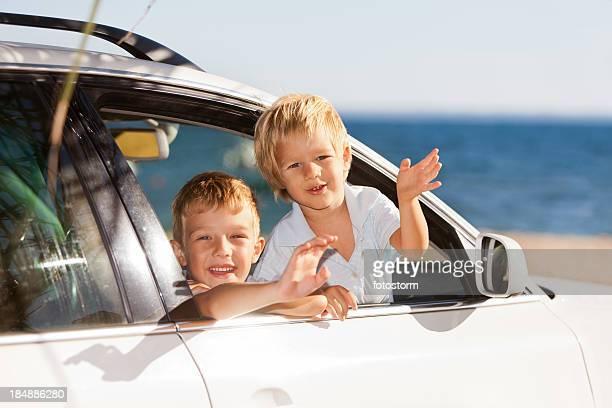 Kinder, die durch ein Fenster im Auto Strand