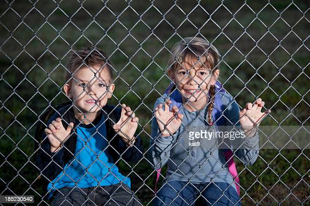 Children looking through chain link fence
