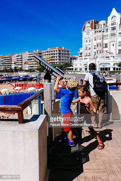 ATLANTIQUES LABOURD FRANCE Children looking through telescope at beach