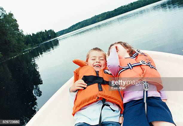 children lying in a boat in a lake - reddingsvest stockfoto's en -beelden