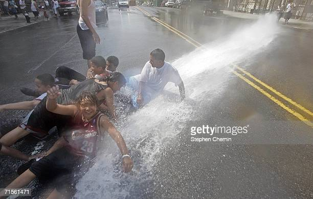 Children lying in the street cool off in the water from a fire hydrant August 1 2006 in New York City After declaring a heat emergency yesterday...