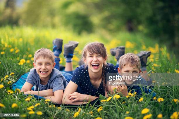 children lying on blanket in beautiful grass - may stock pictures, royalty-free photos & images