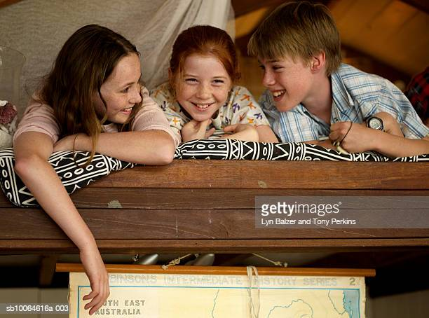 Children (10-11) lying on bunk bed, laughing