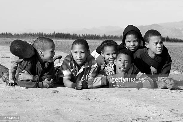 Children lying on dirt road