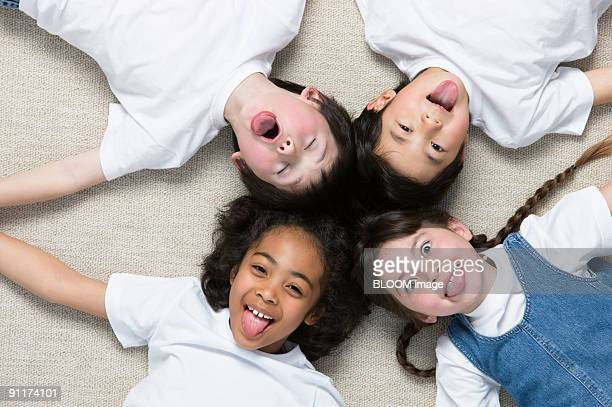 Children lying on floor hand in hand, view from above