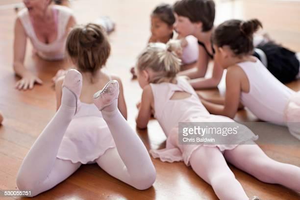 children lying on floor practicing ballet in ballet school - little girls leotards stock photos and pictures