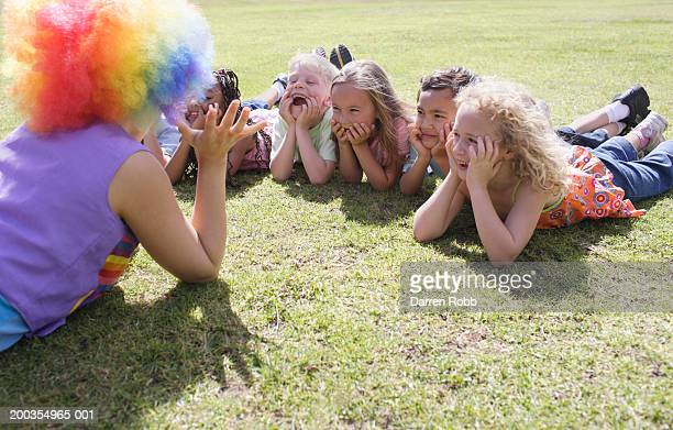 Children (6-7 years) lying on grass, laughing at female clown