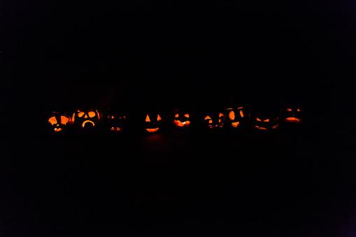 Children made jack o' lanterns at night with orange glow faces - gettyimageskorea