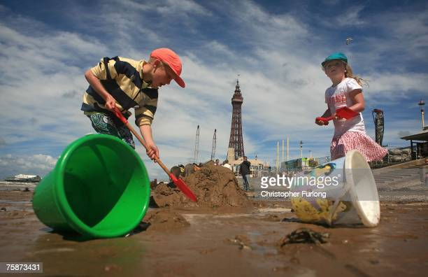 Children make sand castlesl as holiday makers enjoy the warm but windy weather on July 30 Blackpool, England. After the recent floods and unseasonal...