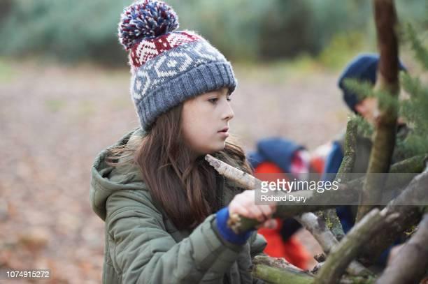 Children making a den  in Autumnal woodland