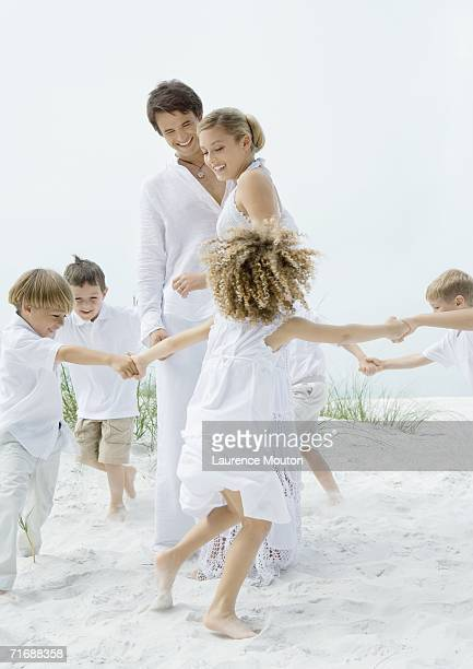 Children making circle around bride and groom on the beach
