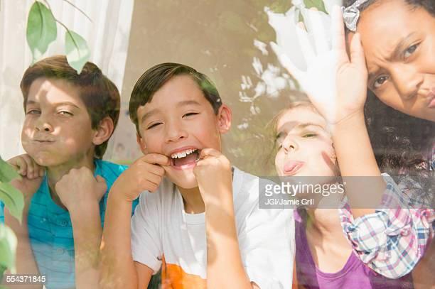Children making faces behind window